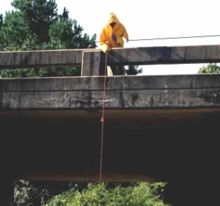 A person with a rain jacket on standing on a bridge while wet weather screening